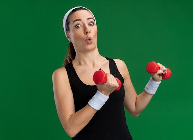 Impressionato giovane donna abbastanza sportiva che indossa fascia e braccialetti che tengono i manubri guardando la parte anteriore isolata sulla parete verde con spazio di copia