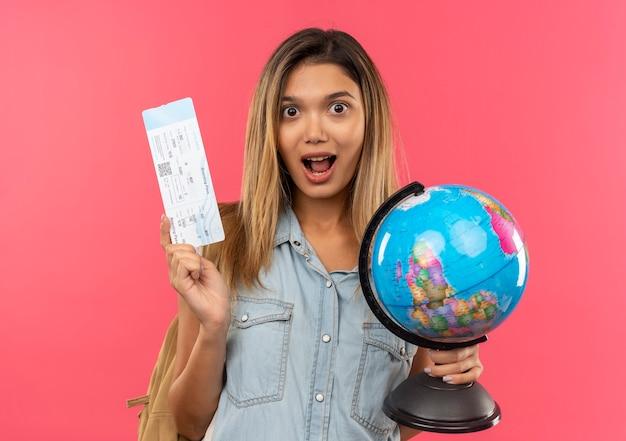 Ragazza graziosa dell'allievo impressionato giovane che porta la borsa posteriore che tiene il biglietto aereo e il globo isolati sul colore rosa
