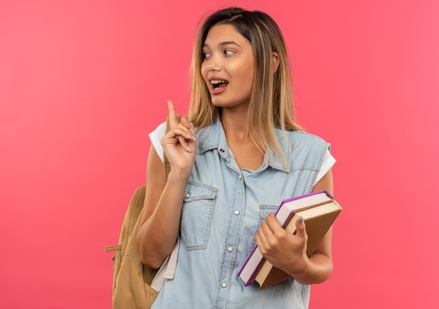 Ragazza giovane graziosa dell'allievo impressionato che porta i libri posteriori della tenuta della borsa che esaminano il lato e che alza il dito isolato sul colore rosa