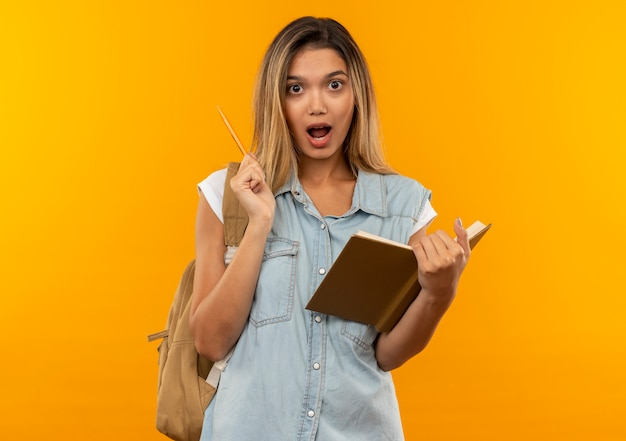 Ragazza graziosa giovane impressionata dell'allievo che porta la borsa posteriore che tiene il libro aperto e la penna isolati sull'arancio