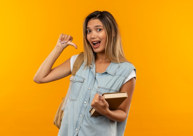 オレンジ色で隔離された自分自身を指している開いた本を保持しているバックバッグを身に着けている感動の若いかわいい学生の女の子