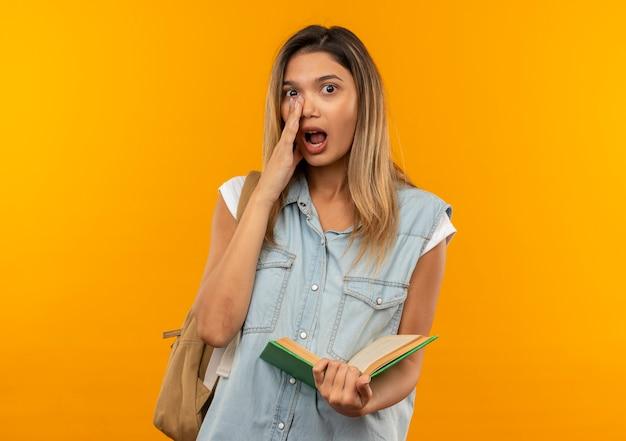 オレンジ色に分離された正面でささやく口の近くに手を置いて開いた本を保持しているバックバッグを身に着けている感動の若いかわいい学生の女の子