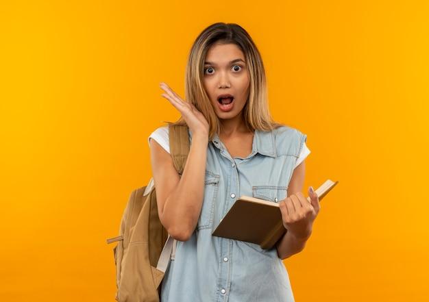 Ragazza graziosa dell'allievo impressionato giovane che porta la borsa posteriore che tiene il libro aperto che mostra la mano vuota isolata sull'arancio