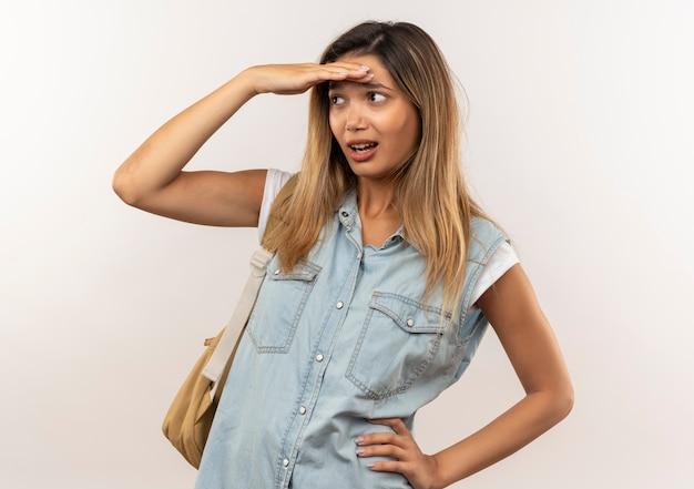 Impressionato giovane studentessa graziosa che indossa la borsa posteriore mettendo la mano sulla vita e sulla fronte guardando la distanza isolata su bianco