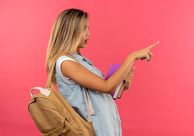 本を保持し、ピンクで隔離されたまっすぐに指している縦断ビューに立っているバックバッグを身に着けている感動の若いかわいい学生の女の子