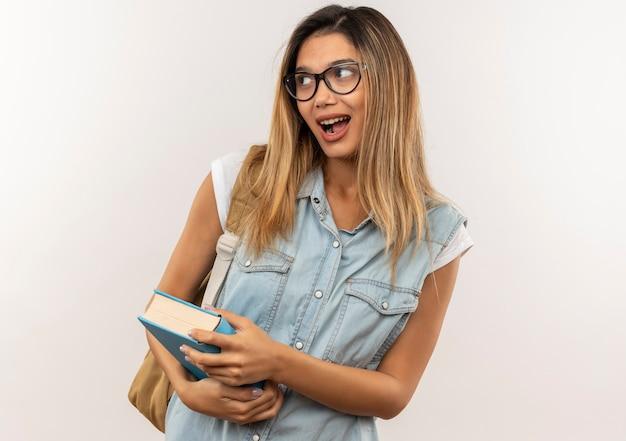 감동 된 젊은 예쁜 학생 소녀 안경을 쓰고 책을 들고 흰색에 고립 된 측면을보고 다시 가방