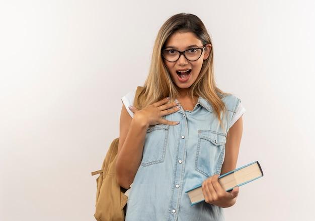 Impressionato giovane ragazza graziosa studentessa con gli occhiali e borsa posteriore che tiene il libro con la mano sulla guancia isolato su bianco