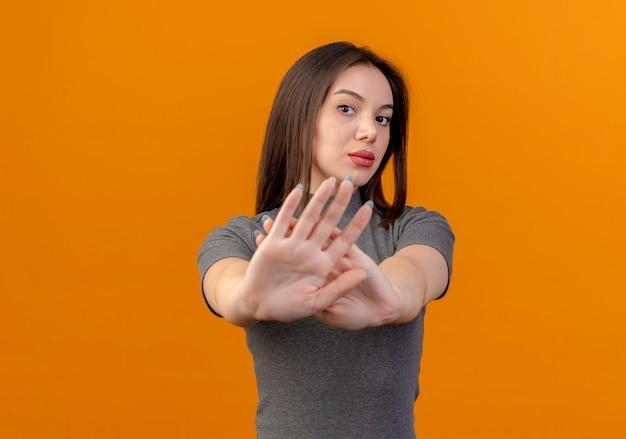 Giovane donna graziosa colpita che non fa alcun gesto alla macchina fotografica isolata su fondo arancio con lo spazio della copia