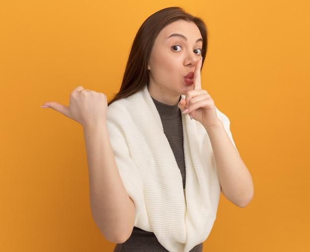Impressionato giovane bella donna che fa gesto di silenzio che punta al lato isolato sul muro arancione