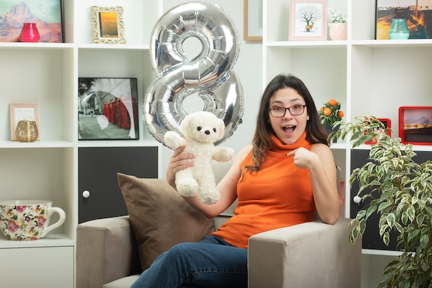 Impressed young pretty woman in glasses holding white teddy bear and pointing at herself sitting on armchair in living room on march international women's day