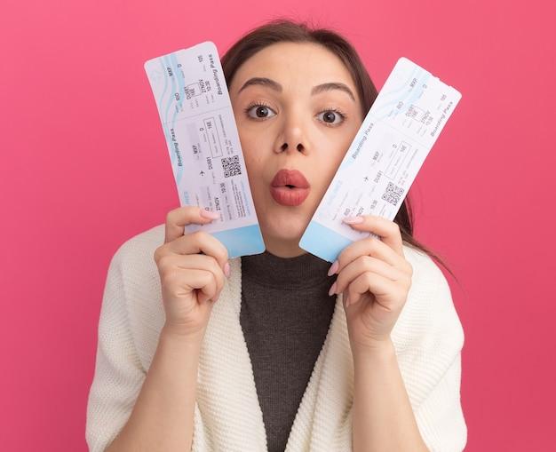ピンクの壁に分離された口すぼめ呼吸で正面を見て彼らと顔に触れる飛行機のチケットを保持している感動の若いきれいな女性