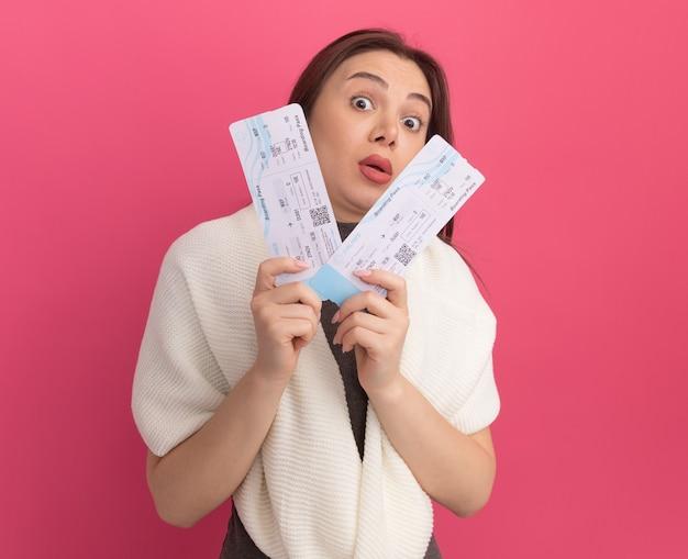飛行機のチケットを持っている感動の若いきれいな女性