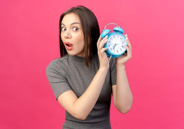 복사 공간 분홍색 배경에 고립 된 알람 시계를 들고 감동 된 젊은 예쁜 여자