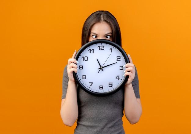 コピースペースでオレンジ色の背景に分離された交差した目で時計を保持し、見て感動若いきれいな女性