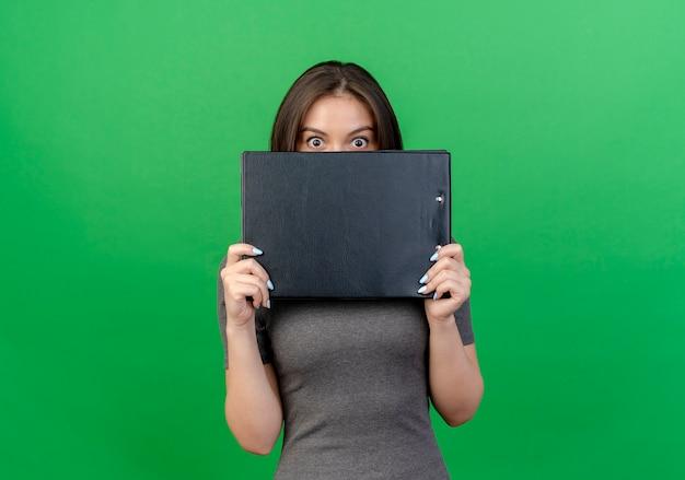 Впечатленная молодая красивая женщина, держащая буфер обмена и смотрящая в камеру сзади, изолированная на зеленом фоне с копией пространства