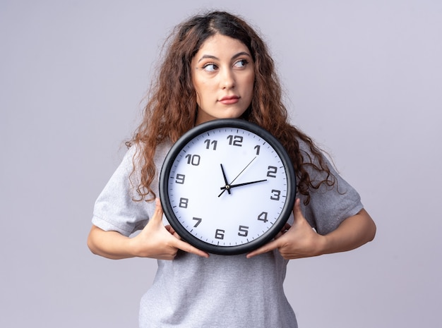 Impressionato giovane donna graziosa che tiene l'orologio guardando il lato isolato sul muro bianco