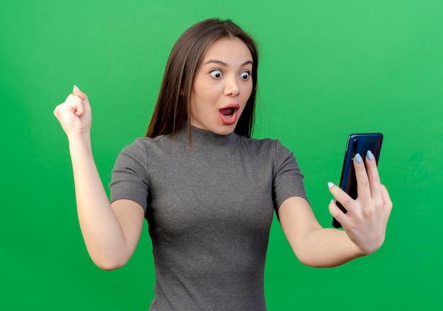 Impressionato giovane donna graziosa che tiene e guardando il telefono cellulare e il pugno di serraggio isolato su sfondo verde