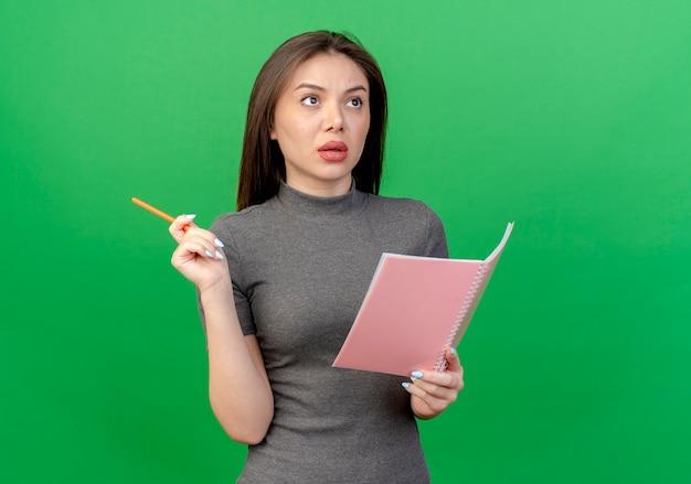 Впечатленная молодая красивая женщина, держащая ручку и блокнот, глядя вверх изолирована на зеленом фоне с копией пространства
