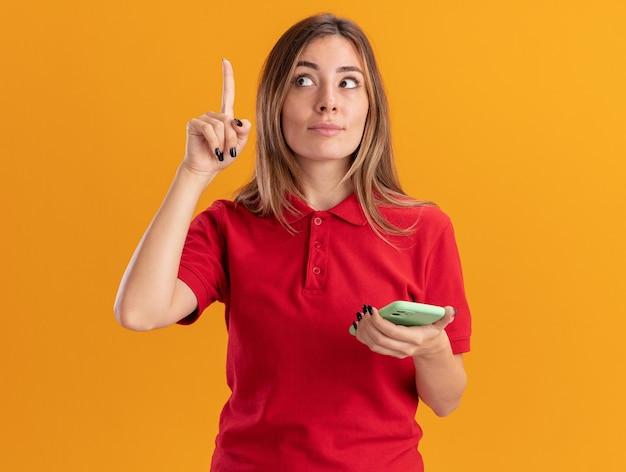 La giovane donna graziosa impressionata tiene il telefono e indica in alto isolato sulla parete arancione