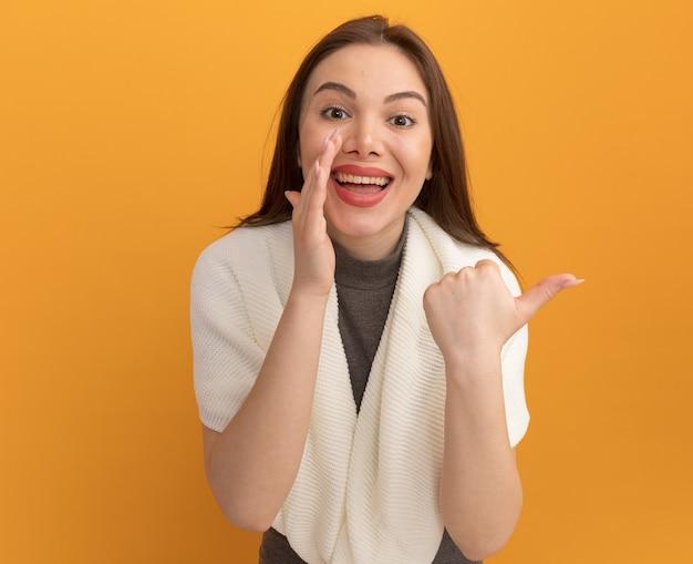복사 공간이 있는 주황색 벽에 격리된 측면을 가리키는 입 근처에 손을 얹고 있는 아름다운 젊은 여성