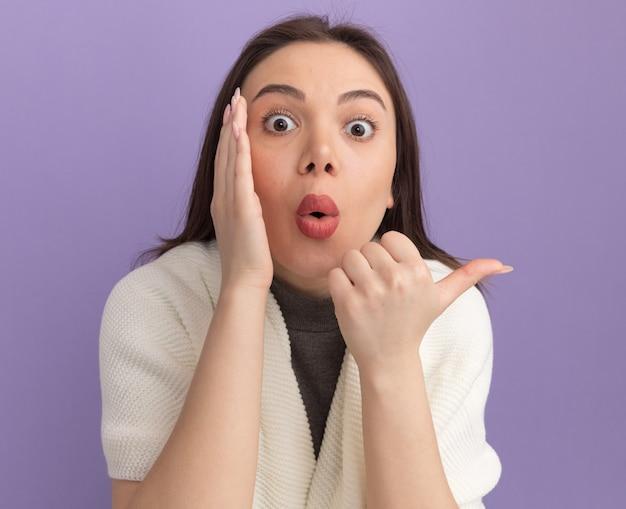 Impressionata giovane bella donna che tiene la mano vicino alla bocca che punta al lato sussurrando isolata sul muro viola