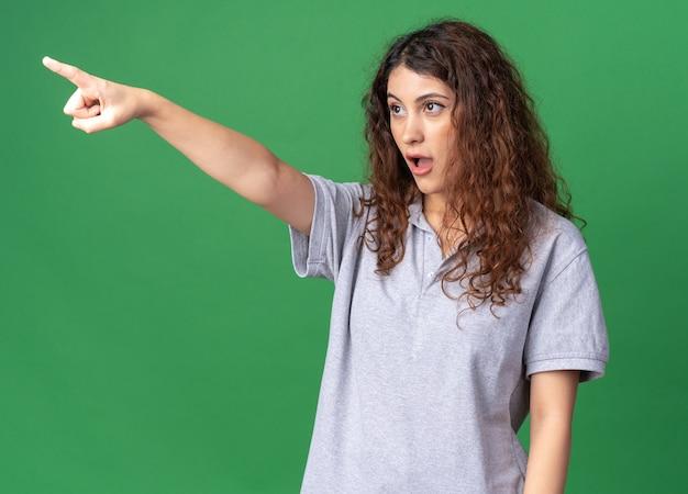 Впечатленная молодая красивая женщина смотрит и указывает на сторону, изолированную на зеленой стене