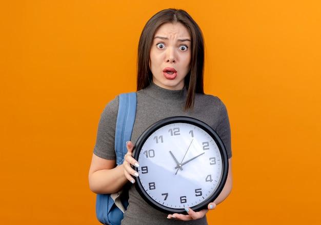 Впечатленная молодая красивая женщина в задней сумке, держащая часы, изолированные на оранжевом фоне с копией пространства