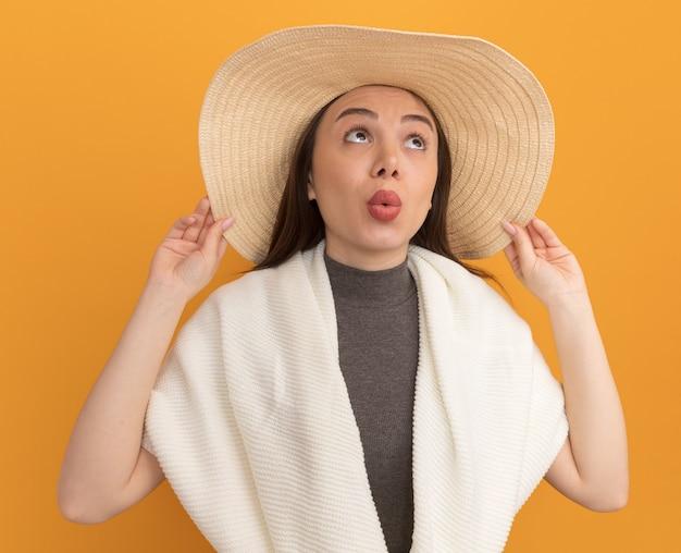 Впечатленная молодая красивая женщина в пляжной шляпе, хватая шляпу, глядя вверх со сжатыми губами