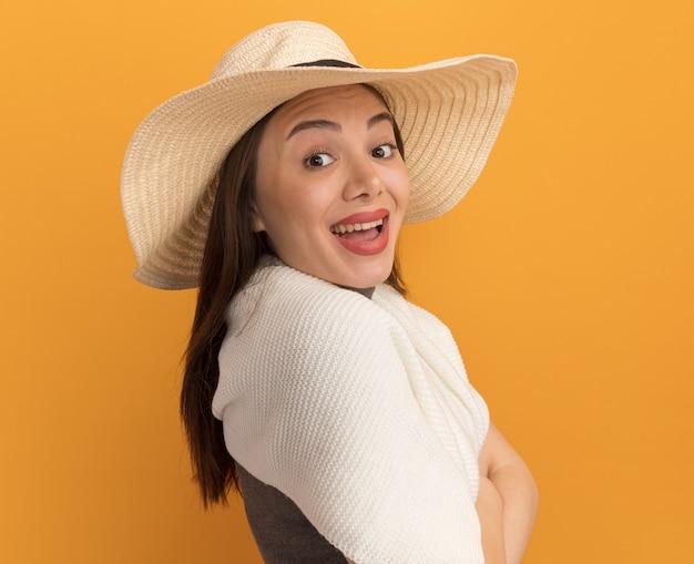 Impressionato giovane bella donna che indossa un cappello da spiaggia in piedi in vista di profilo isolato su parete arancione