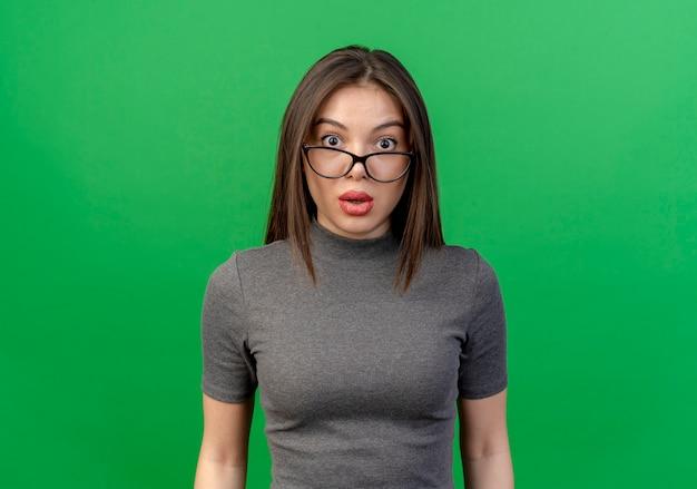 Impressionato giovane donna graziosa con gli occhiali isolati su sfondo verde con spazio di copia