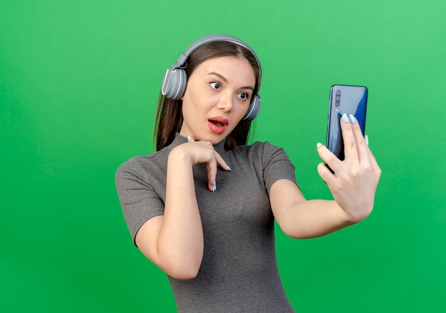Впечатленная молодая красивая женщина в наушниках, держащая и смотрящая на мобильный телефон и держащая руку на груди, изолированную на зеленом фоне с копией пространства