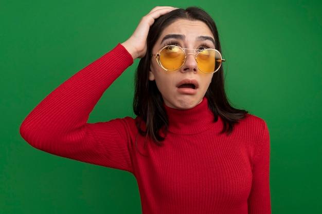 Impressionato giovane bella donna che indossa occhiali da sole tenendo la mano sulla testa guardando in alto isolato sul muro verde