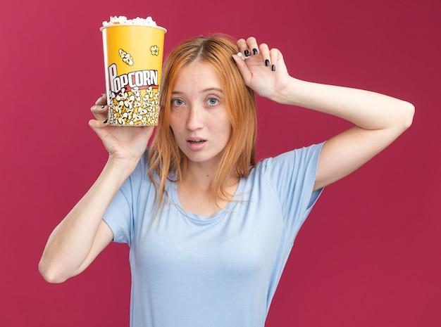 Ha impressionato la giovane ragazza rossa dello zenzero con le lentiggini che tengono il secchio del popcorn vicino al viso sul rosa