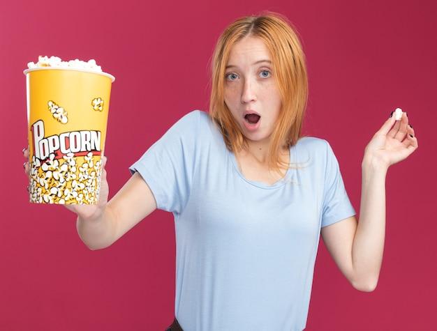 Impressionata giovane ragazza rossa allo zenzero con le lentiggini tiene in mano un secchio di popcorn