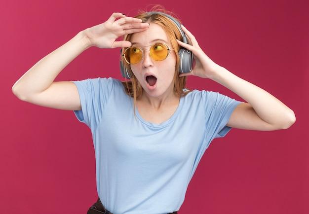 サングラスとヘッドフォンでそばかすのある印象的な若い赤毛の生姜の女の子は、ピンクの側を見て額に手のひらを保ちます