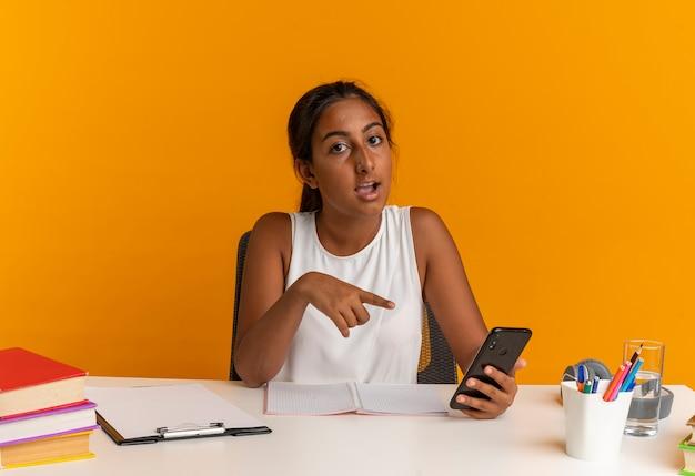 Впечатленная молодая школьница сидит за столом со школьными принадлежностями и указывает на телефон