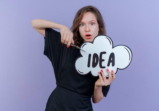 보라색 배경에 고립 된 아이디어 거품과 가위를 들고 유니폼을 입고 감동 젊은 슬라브 여성 이발사
