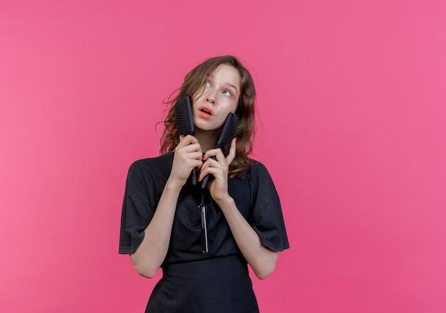コピースペースでピンクの背景に分離された側を見て櫛で均一なタッチの顔を身に着けている印象的な若いスラブ女性理髪師