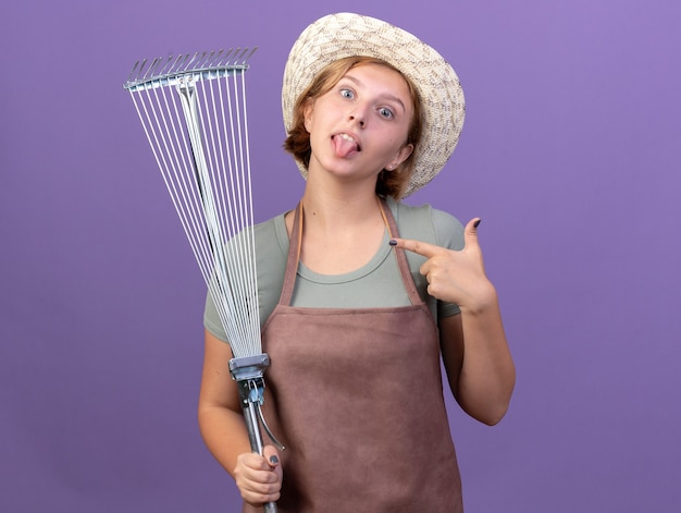 Impressed young slavic female gardener wearing gardening hat stucks out tongue holding and pointing at leaf rake on purple