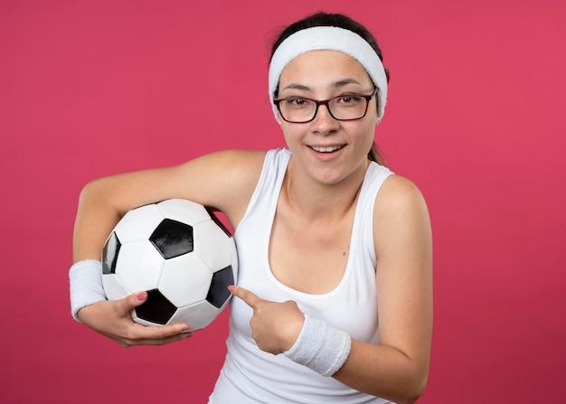 ヘッドバンドを身に着けている光学メガネで感銘を受けた若いスポーティな女の子