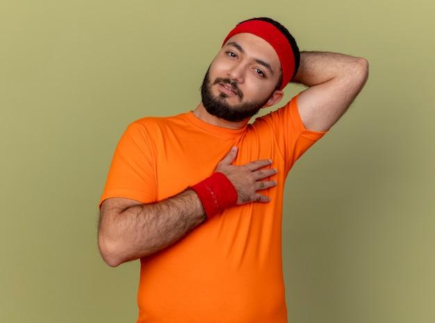 Impressionato giovane sportivo che guarda l'obbiettivo indossando la fascia e il braccialetto mettendo le mani sul collo e sul petto isolato su sfondo verde oliva