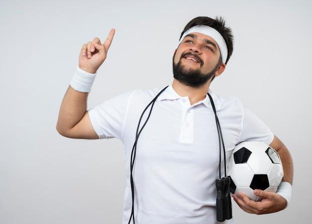 白い壁に隔離された上でボールポイントを保持している肩に縄跳びとヘッドバンドとリストバンドを身に着けている感動の若いスポーティな男