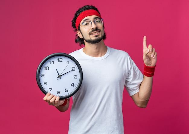 壁時計のポイントを上に保持しているリストバンドとヘッドバンドを身に着けている感銘を受けた若いスポーティな男