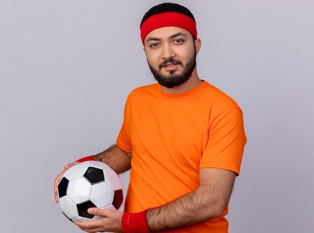 Ha impressionato il giovane sportivo che indossa la fascia e la sfera della tenuta del braccialetto isolata su fondo bianco