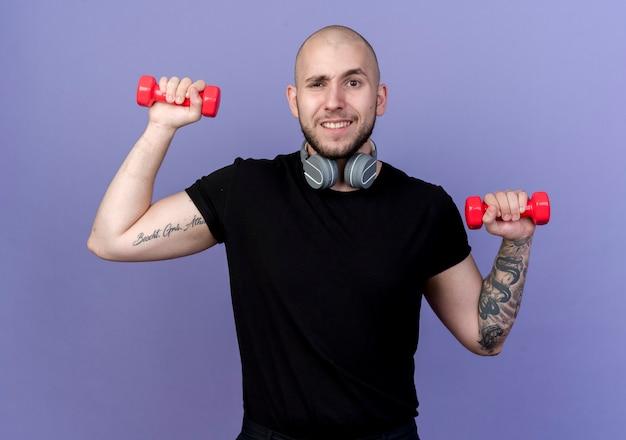 헤드폰을 착용하고 보라색 벽에 고립 된 아령으로 운동하는 감동 된 젊은 스포티 한 남자