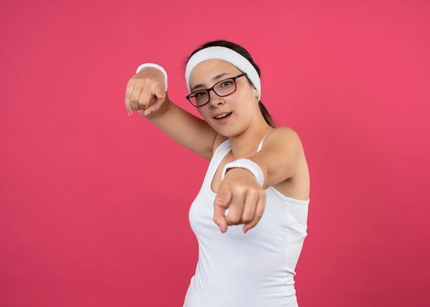Impressionato giovane donna sportiva con occhiali ottici che indossa fascia e braccialetti che punta sul davanti isolato sul muro rosa