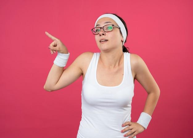 La giovane donna sportiva impressionata con gli occhiali ottici indossa la fascia e i braccialetti mette la mano sulla vita e punta sul lato isolato sul muro rosa
