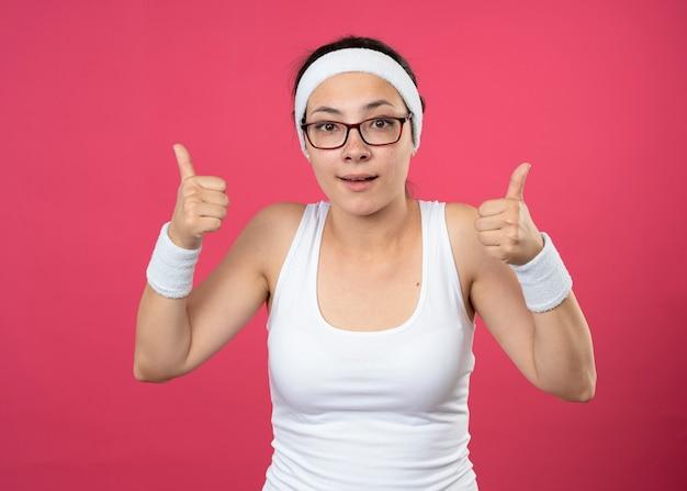 Impressionato giovane donna sportiva in occhiali ottici che indossa la fascia e braccialetti pollici in su con due mani isolate sul muro rosa