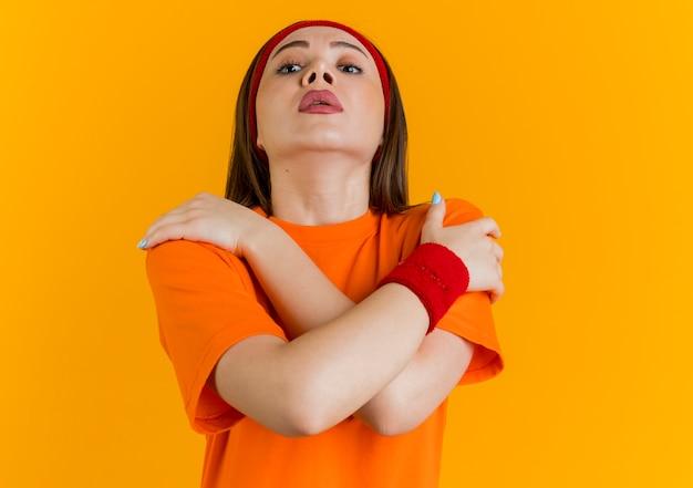 コピースペースのあるオレンジ色の壁で隔離された肩に手を交差させたままヘッドバンドとリストバンドを身に着けている感動の若いスポーティな女性