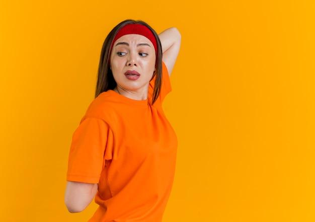 Впечатленная молодая спортивная женщина с головной повязкой и браслетами, стоящая в профиле, глядя в сторону, держа руки за спиной, упражнения изолированы на оранжевой стене с копией пространства